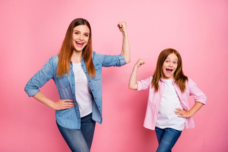 Portrait of cheerful superheros with long hair screaming raising fists isolated over pink background. Portrait of cheerful, superheros with long hair screaming stock photos