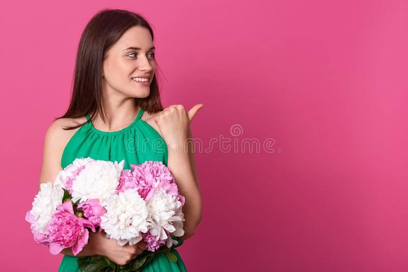 Portrait of cheerful tender model standing isolated over pink background in studio, making gesture, showing with thumb aback, stock image