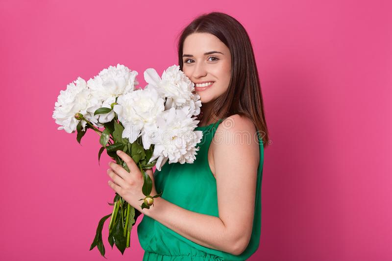 Portrait of cheerful tender model standing isolated over pink background in studio, smelling and putting close to face peonies, stock photo