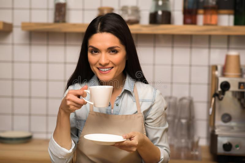 Waitress holding cup of coffee. Portrait of cheerful Waitress holding cup of coffee and looking at the camera royalty free stock image