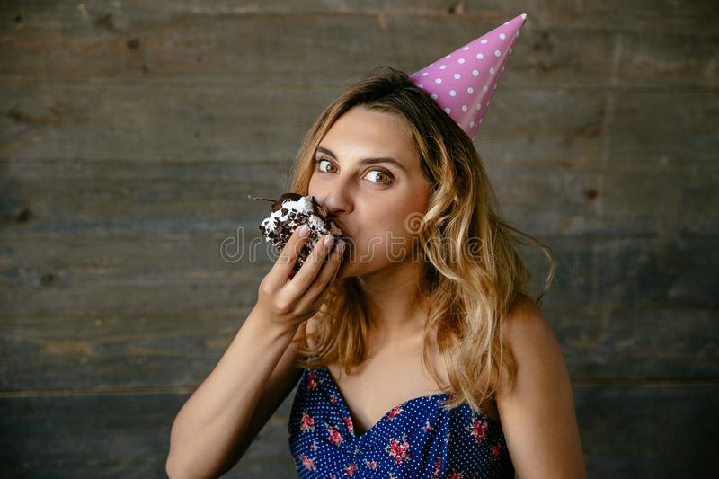 Beautiful girl eating a piece of birthday cake. Portrait of a cheerful woman eating chocolate cake, celebrating birthday, looking at camera, in holiday hat royalty free stock image