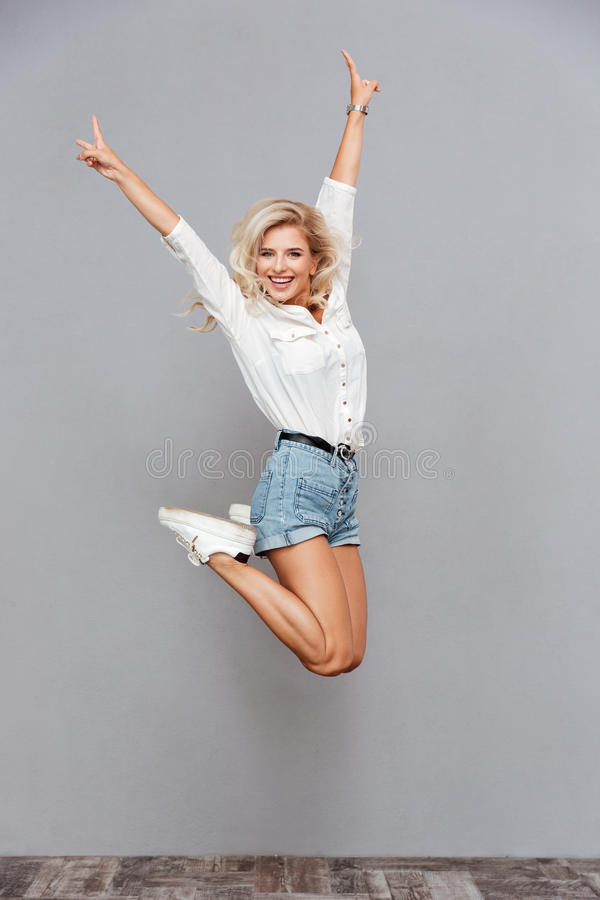 Portrait of a cheerful woman jumping and showing v gesture stock photography