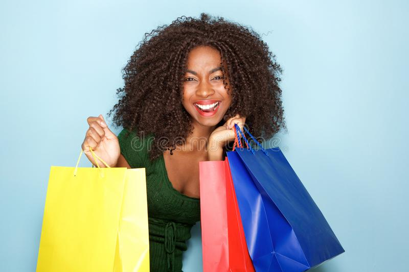 Cheerful young african woman with shopping bags on blue background royalty free stock photography