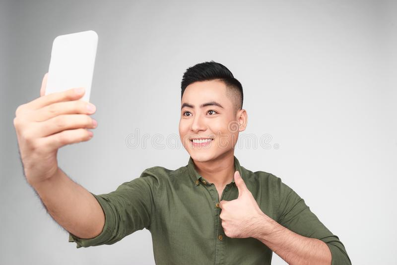 Portrait of a cheerful young asian man taking selfie photo again stock photography