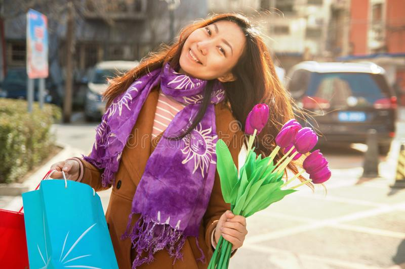 Portrait of cheerful young woman with beautiful purple tulips. stock photos