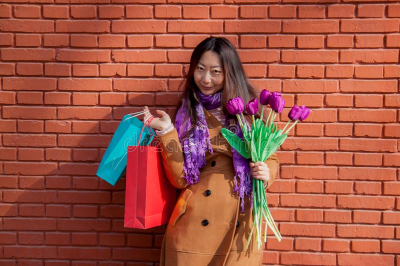 Portrait of cheerful young woman with beautiful purple tulips. royalty free stock photos