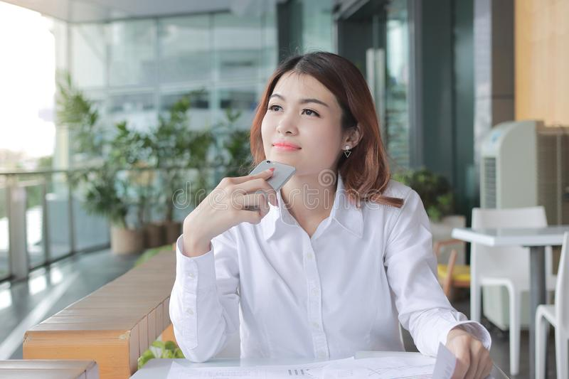 Portrait of cheerful young Asian woman looking forward and have an idea in office royalty free stock image