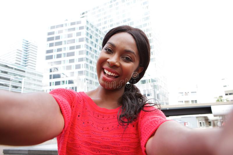 Cheerful young black woman taking selfie in the city. Portrait of cheerful young black woman taking selfie in the city royalty free stock photos