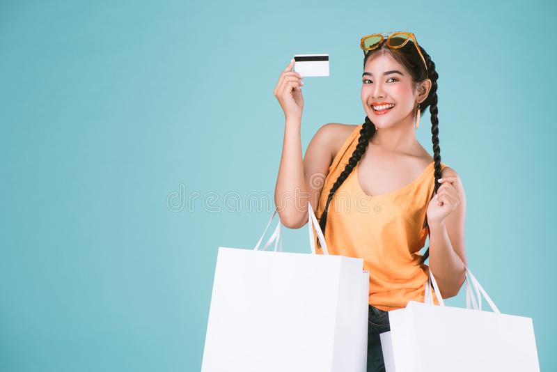 Portrait of cheerful young brunette woman holding credit card and shopping bags. stock images