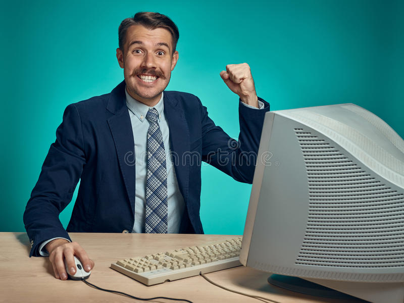 Portrait of cheerful young businessman sitting with computer. Portrait of cheerful happy young businessman sitting with computer on blue studio stock photos