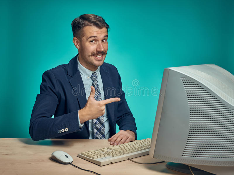 Portrait of cheerful young businessman sitting with computer. Portrait of cheerful happy young businessman sitting with computer on blue studio stock images
