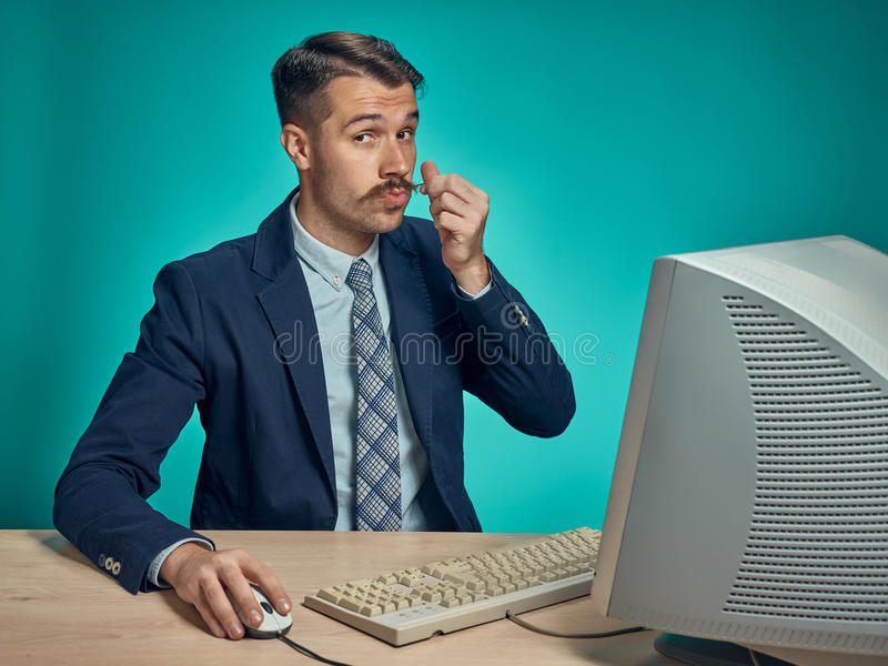 Portrait of cheerful young businessman sitting with computer. Portrait of cheerful happy young businessman sitting with computer on blue studio stock photo