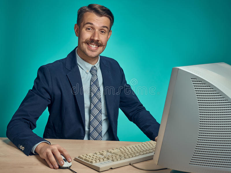 Portrait of cheerful young businessman sitting with computer. Portrait of cheerful happy young businessman sitting with computer on blue studio royalty free stock images