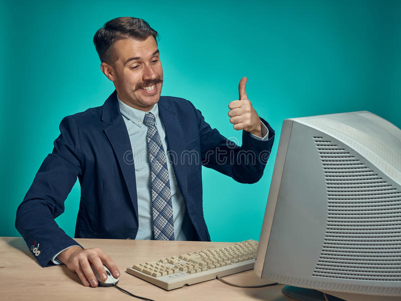 Portrait of cheerful young businessman sitting with computer. Portrait of cheerful happy young businessman sitting with computer on blue studio and showing sign royalty free stock photos