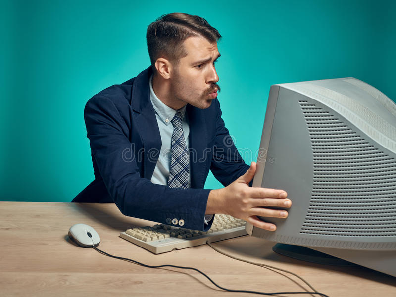 Portrait of cheerful young businessman sitting with computer. Portrait of cheerful happy young businessman sitting with computer and kissing monitor on blue stock photography