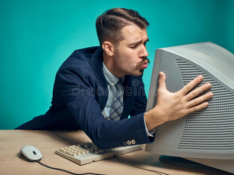Portrait of cheerful young businessman sitting with computer. Portrait of cheerful happy young businessman sitting with computer and kissing monitor on blue royalty free stock photos