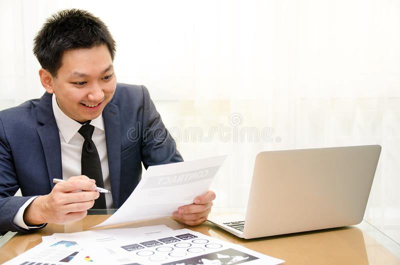 Portrait of cheerful young businessman working on the laptop at creative office stock photo