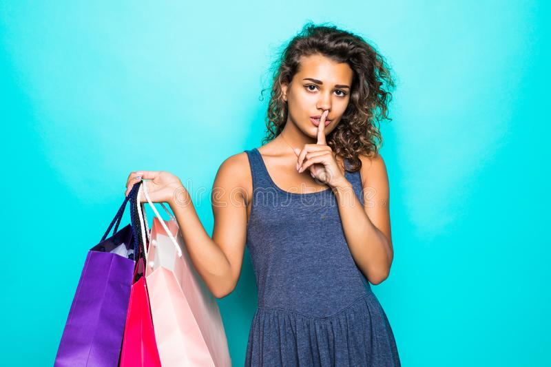 Portrait of a cheerful young curly latin woman standing carrying shopping bags, showing silence gesture isolated over green backgr stock photo