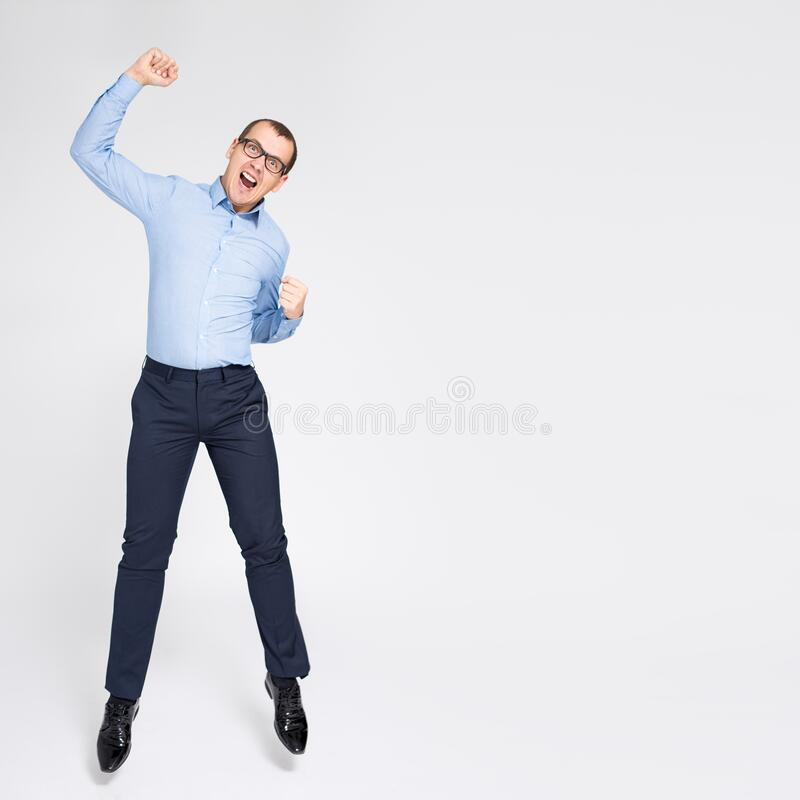 Portrait of cheerful young handsome businessman celebrating something and jumping over gray background royalty free stock photo