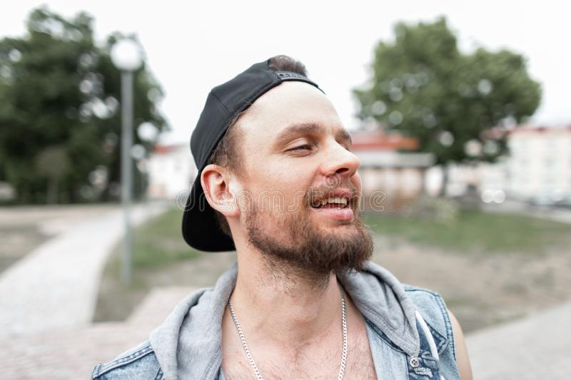 Portrait of a cheerful young man with a beard smiling in a stylish black cap in a fashionable blue denim vest in the city. royalty free stock images