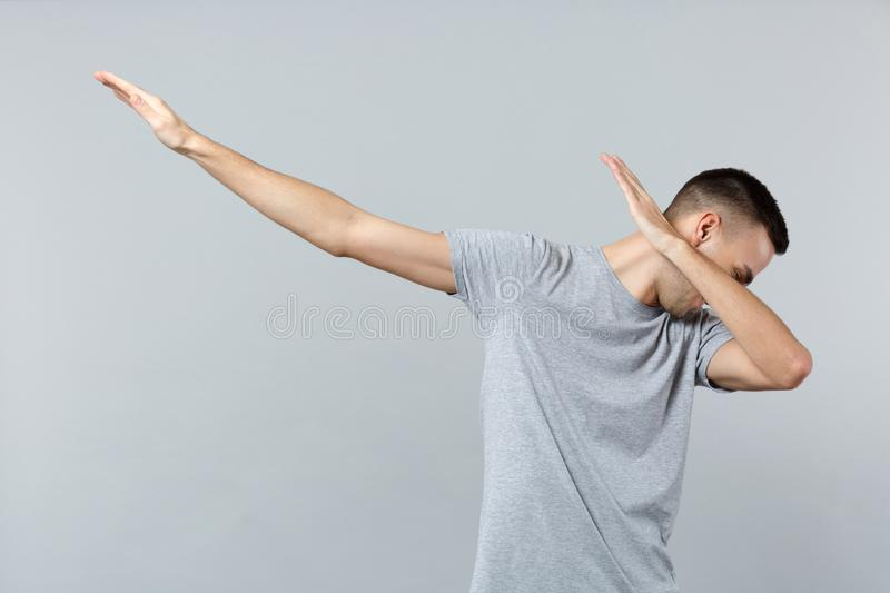 Portrait of cheerful young man in casual clothes showing dab dance gesture isolated on grey wall background in studio. People sincere emotions, lifestyle royalty free stock photography