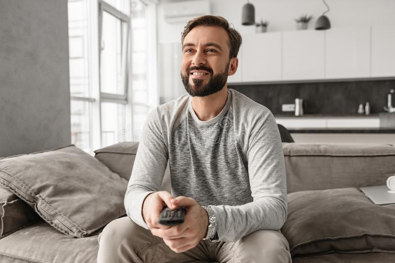 Portrait of a cheerful young man holding TV remote control stock photography