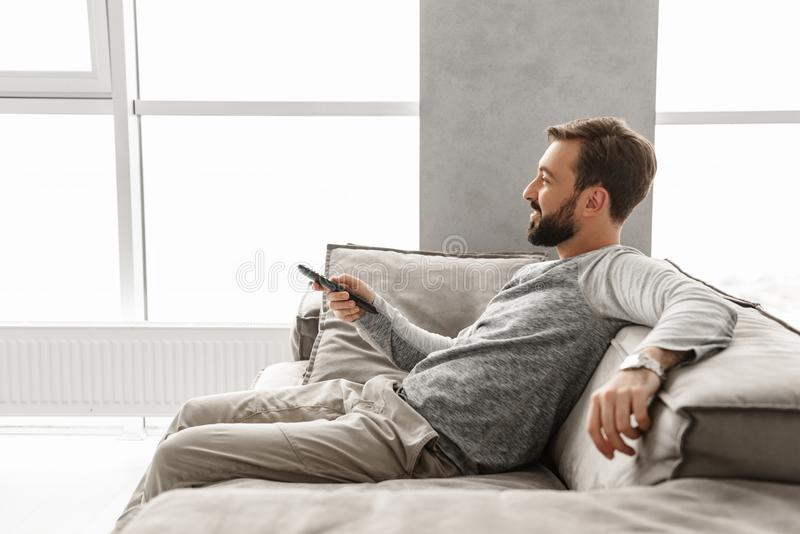 Portrait of a cheerful young man holding TV remote control royalty free stock photos