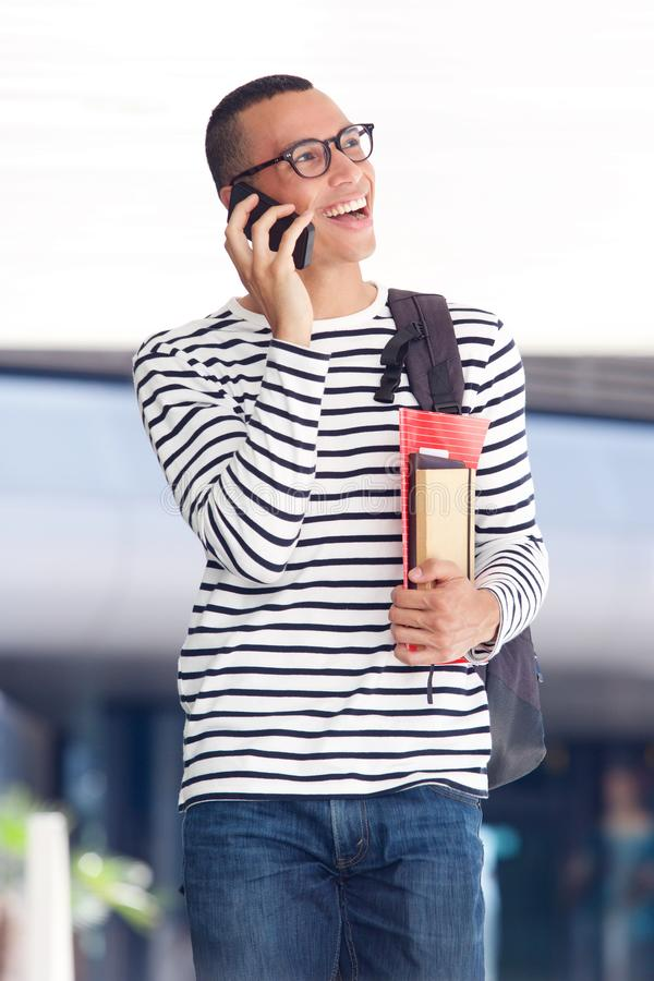 Cheerful young man laughing while talking on mobile phone at college campus. Portrait of cheerful young man laughing while talking on mobile phone at college royalty free stock photography