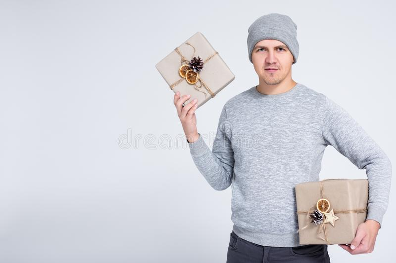 Portrait of cheerful young man in warm winter clothes posing with gift box over gray background with copy space royalty free stock image