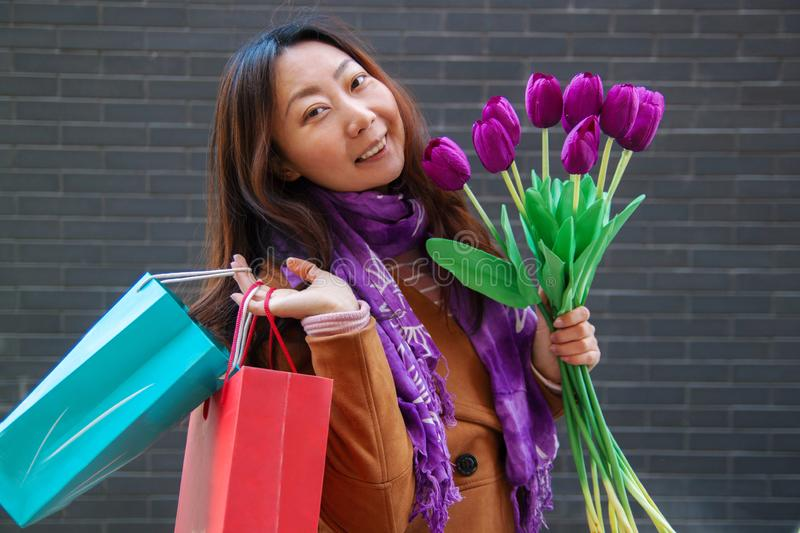 Portrait of cheerful young woman with beautiful purple tulips. royalty free stock photo