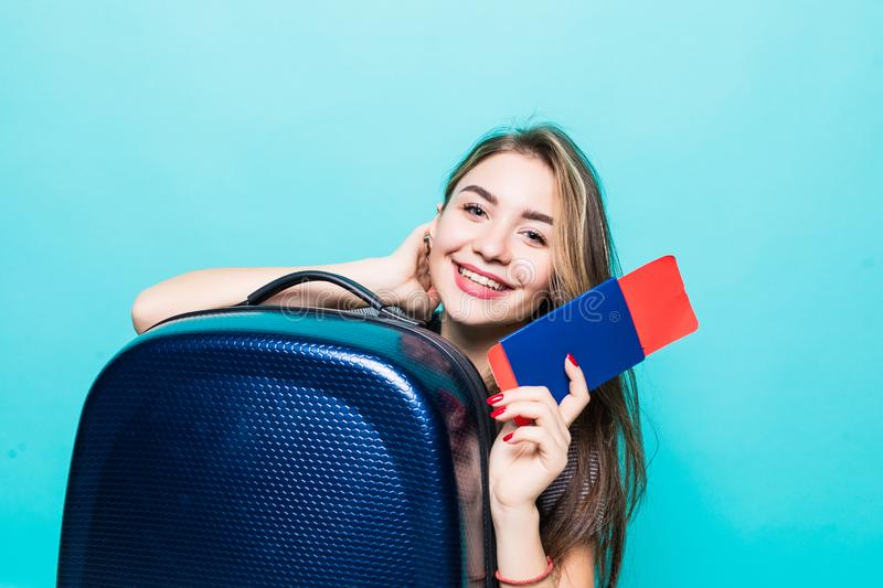 Portrait of a cheerful young woman dressed in summer clothes holding passport with flying tickets while standing with a suitcase. Portrait of woman holding royalty free stock photography