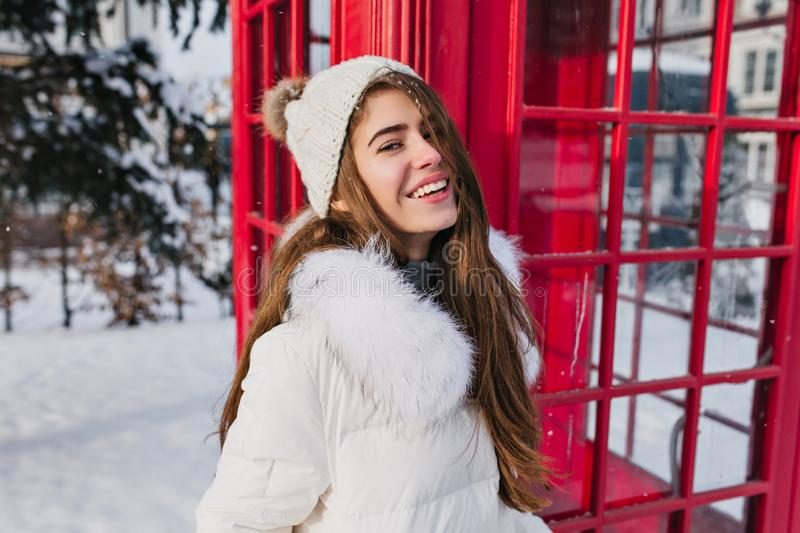 Portrait cheerful young woman in knitted warm hat with long brunette hair enjoying winter frozen weather on street on royalty free stock image