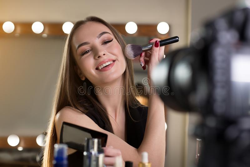 Optimistic girl is powdering her face royalty free stock image