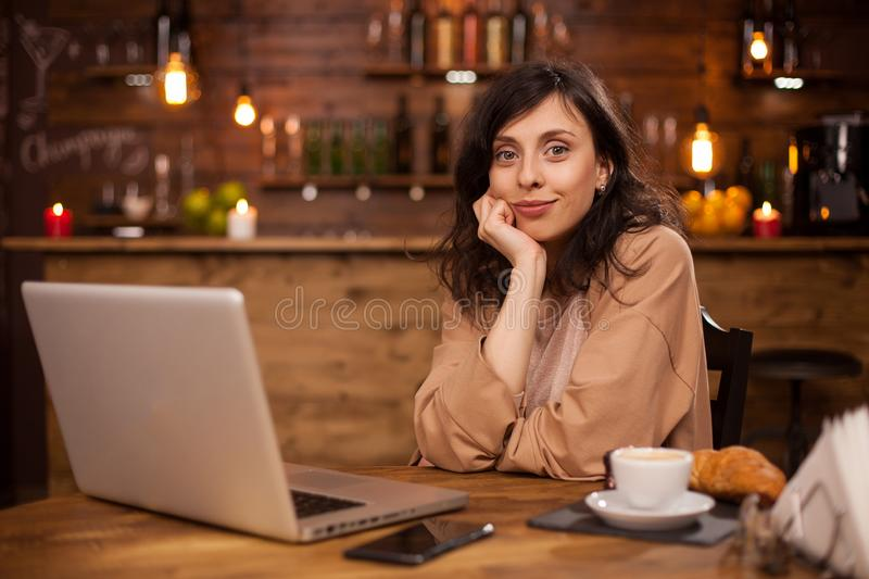 Portrait of cheerful young woman sitting down in a coffee shop smilling at the camera royalty free stock photography