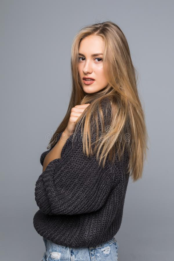 Portrait of a cheerful young woman in sweater smiling with arms crossed on gray background royalty free stock photos