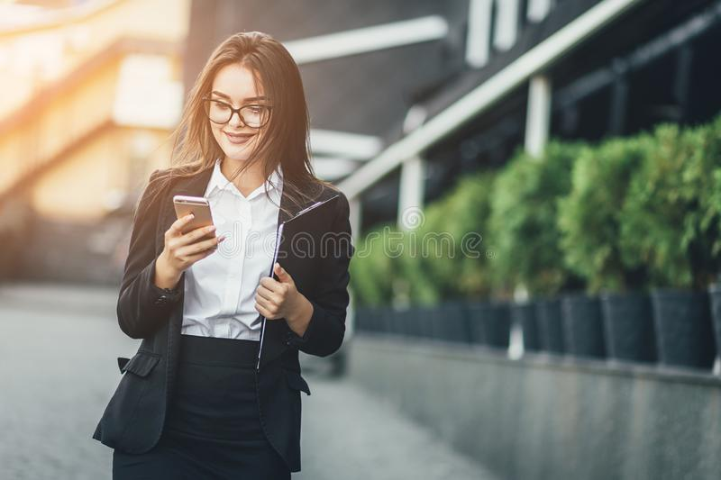 Portrait of cheerful young woman talking on smartphone and laughing outdoors. Happy beautiful caucasian woman using stock images
