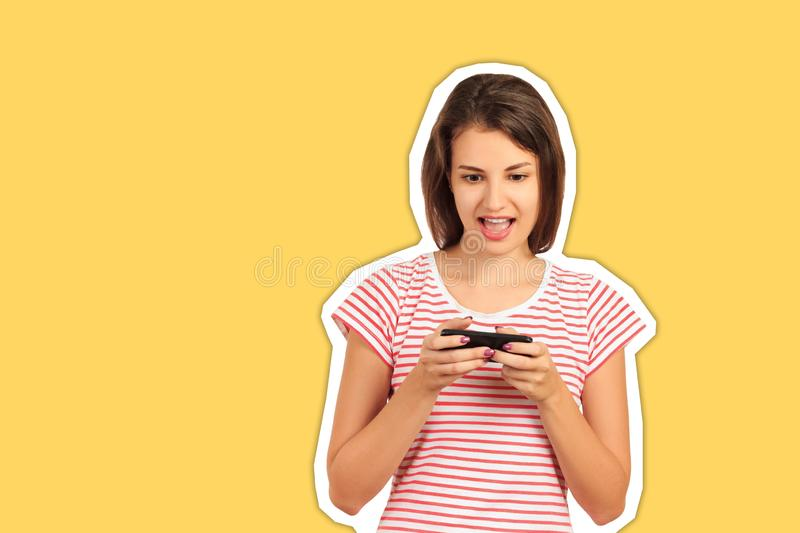 Portrait of a cheerful young woman using a mobile phone playing a game on the network. emotional girl Magazine collage style with royalty free stock image