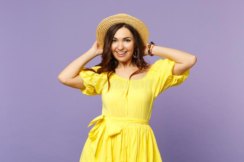 Portrait of cheerful young woman in yellow dress putting hands on summer hat, looking camera isolated on pastel violet stock photos