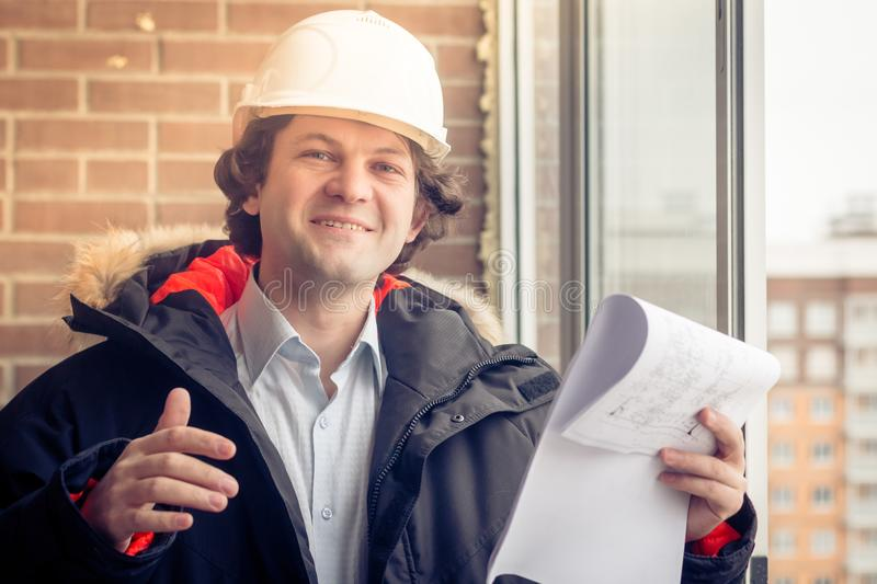 Portrait of cheerful young worker wearing hardhat posing looking at camera and smiling enjoying work on brick background royalty free stock photography