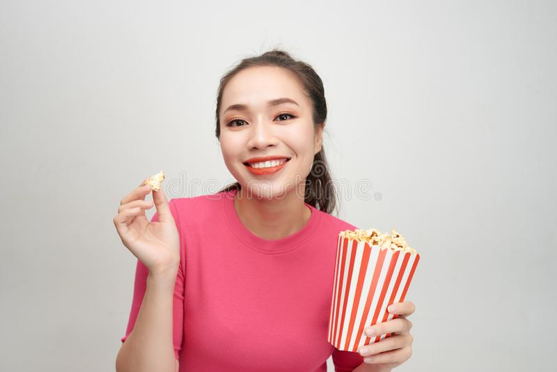 Portrait of a cheery pretty girl eating popcorn isolated over white background stock photos