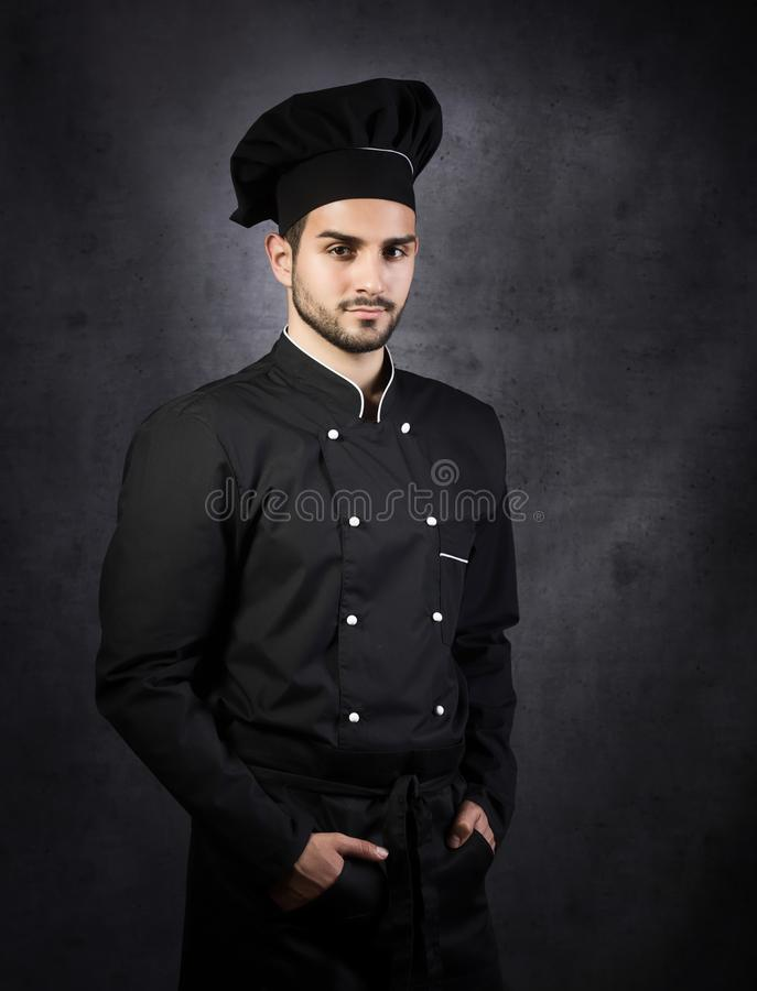 Portrait of a chef cooker in black uniform. stock photos