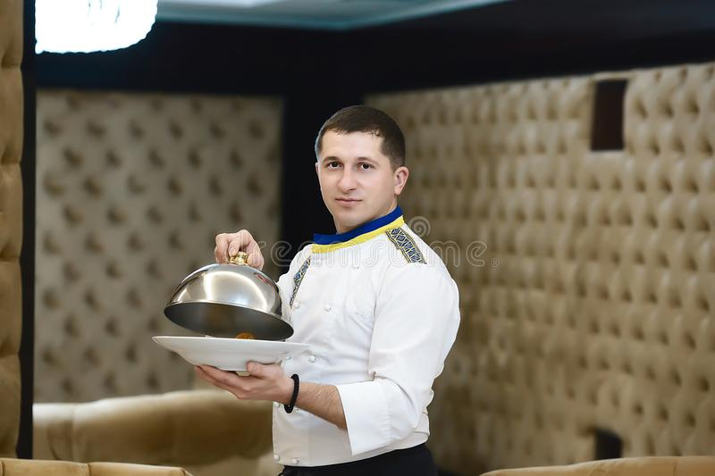 Portrait chef presenting a dish at the hotel restaurant, steaming a dish with a cover lid royalty free stock photo