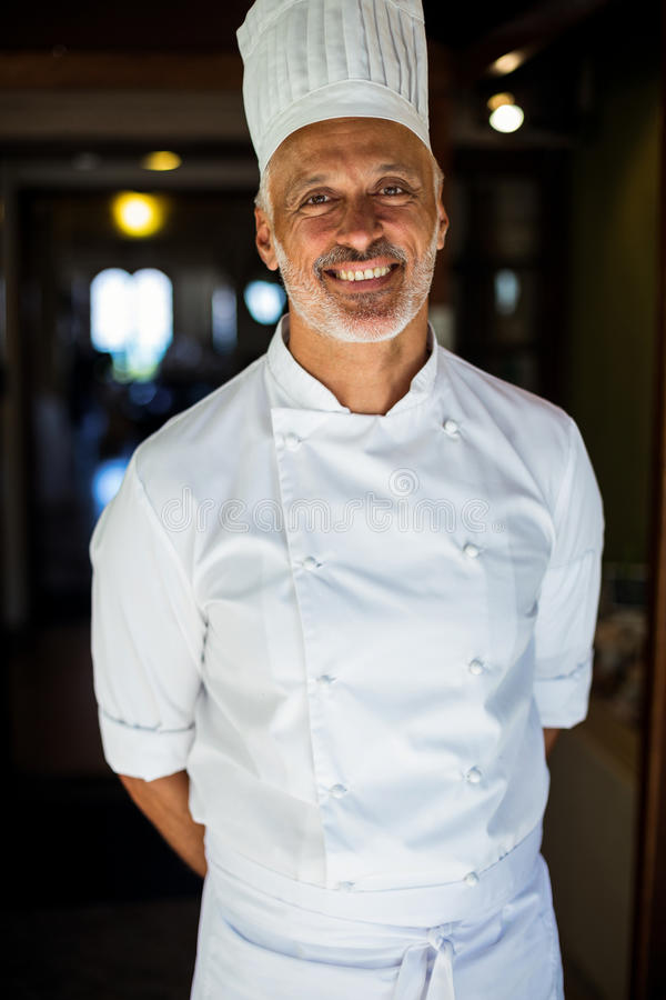 Portrait of chef standing with hands behind back. In restaurant royalty free stock photos