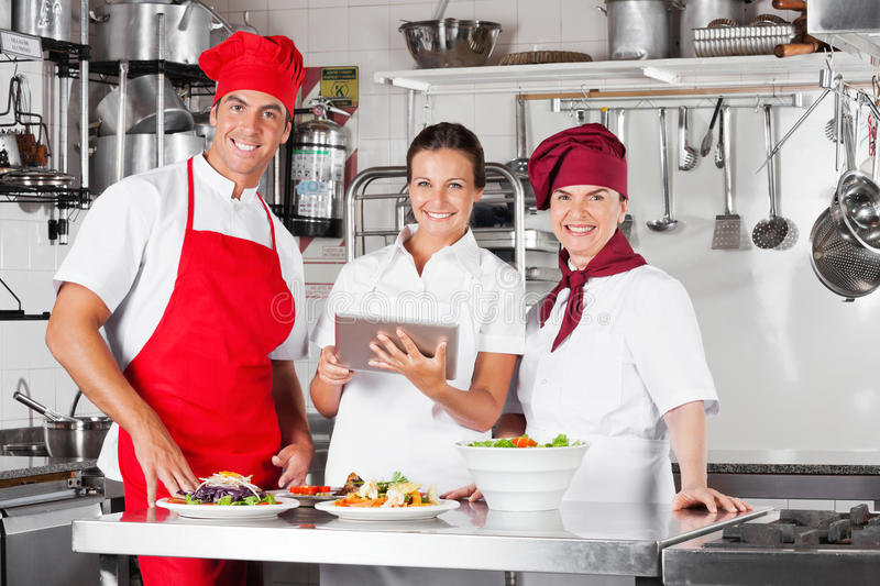 Download Happy Chefs Using Tablet Computer In Kitchen Stock Photo - Image: 29893498