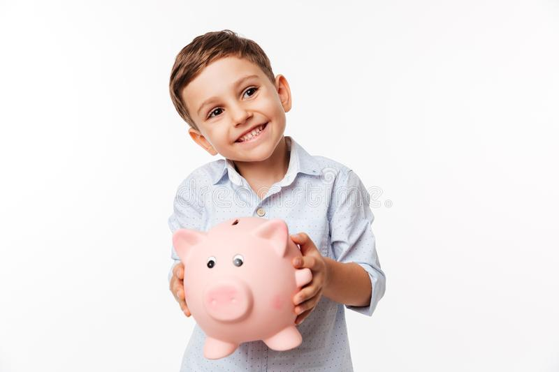 Portrait of a cherry cute little kid holding piggy bank. And looking away at copy space isolated over white background stock image