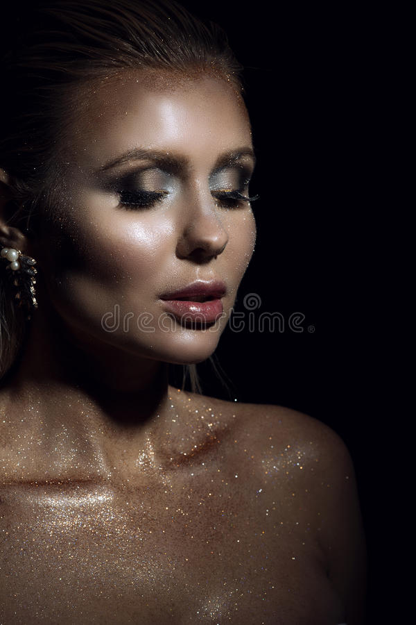Portrait of chic gorgeous blond woman with wet hair and artistic glittering make-up looking down with her full lips parted. On black background. Close up stock photos