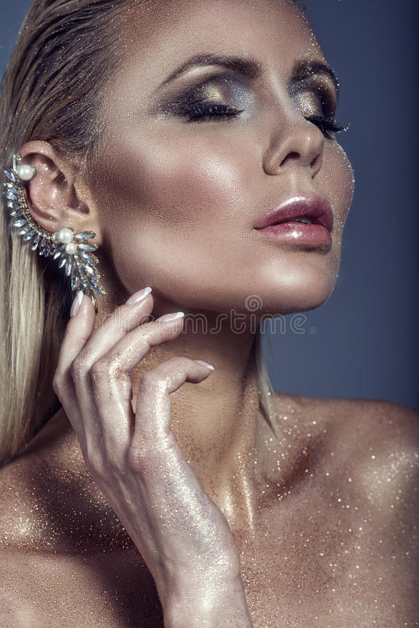 Portrait of chic gorgeous blond woman with wet hair and artistic glittering make-up touching the cuff on her ear with close eyes stock images
