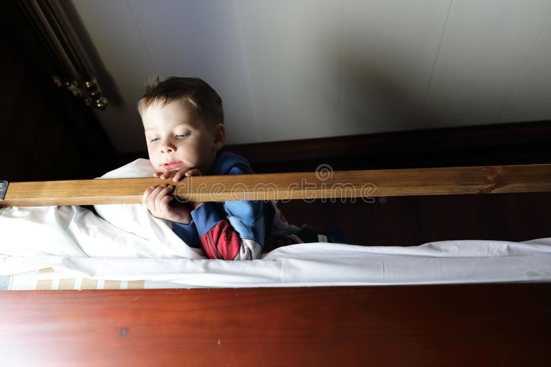 Child on bed in cabin of ship royalty free stock image
