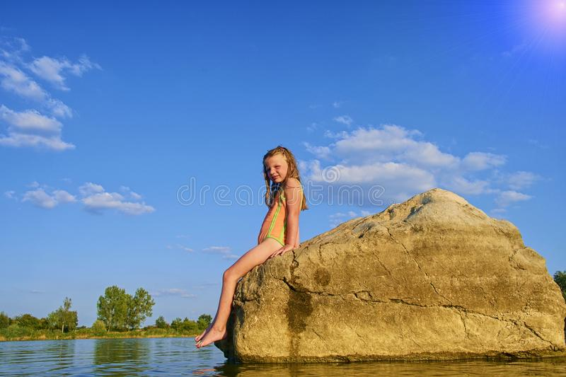 Portrait of child blond girl posing in swimsuit on rocks inside the lake at sunset. Summer and happy childhood concept royalty free stock photo
