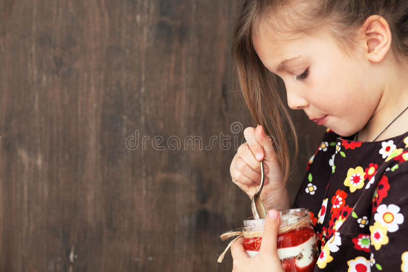 Child eating dessert. Portrait of a child eating sweet homemade dessert with berries royalty free stock image